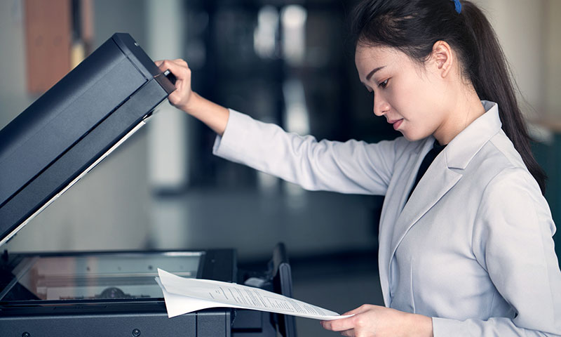 Girl with document at printer copier
