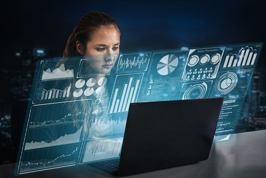 Analyst working on laptop with charts and graphs