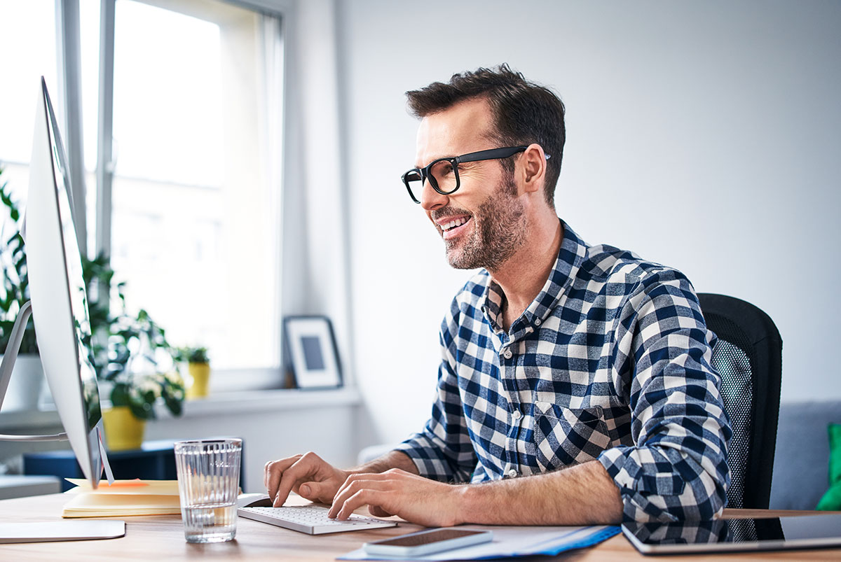 Smiling man working productively from home office